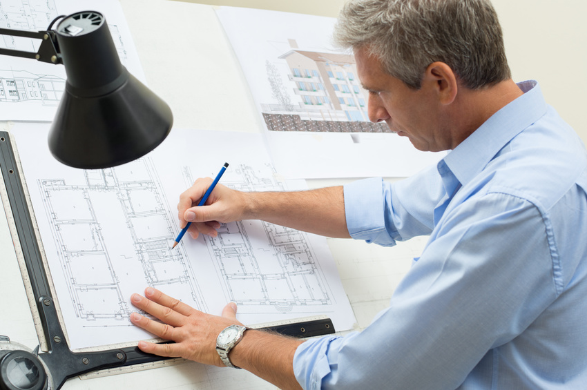 Portrait Of Male Architect Working On Blueprint At Office